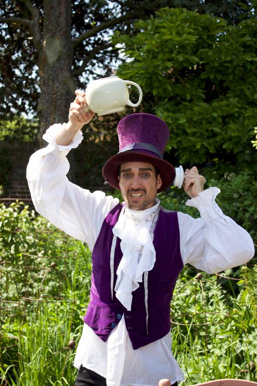 Sam John as the Hatter taking an urgent call